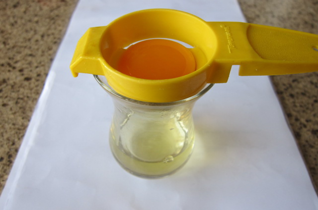 using a tool to seperate egg yolk and egg white